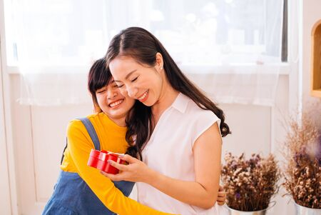 Smiling happy Asian teenage daughter and Asian middle-aged mother hugging together in indoor living room at home. Mum is holding a present gift. Stock fotó