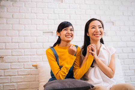 Asian family of mother and daughter smiling while cheering at home and watching TV on white brick wall background