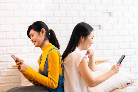 Side view of smiling Asian women sitting back to back on bed and browsing in cellphones on brick wall background. Watching entertainment, social media, wireless communication concept