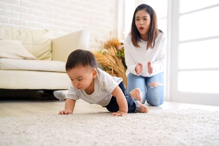 Serious Asian little boy crawling on floor while young mother sitting behind cheering up and clapping hands in light living room