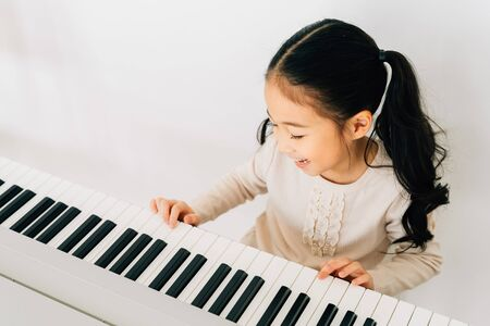 From above of happy smiling cute Asian girl playing piano enjoying time practicing music at home Stock fotó