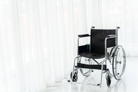 Black empty wheelchair on tiled floor with white draperies on background at modern hospital Stock fotó