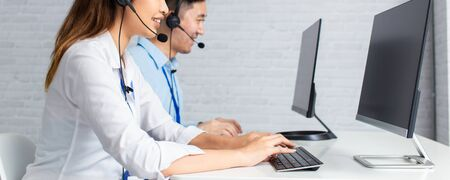 Banner of cheerful Asian man and woman in headsets smiling and typing on computer keyboard while working in office of call center