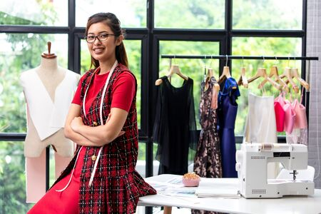 Young Asian fashion designer smiling and looking at camera in front of working desk. Self-employed dressmaker with mannequin, sewing machine, and hanging dresses. Stock fotó