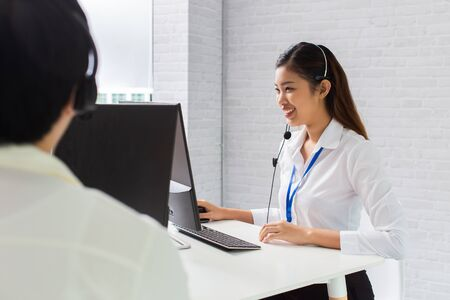 Cheerful Asian man and woman in headsets smiling and typing on computer keyboard while working in office of call center company