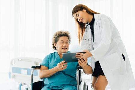 Young Asian physician in uniform showing and explaining test results on digital tablet to elderly female patient on wheelchair at hospital Stock fotó