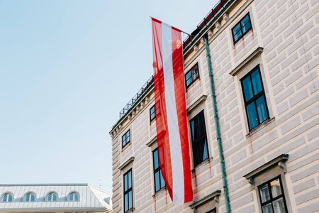 From below of old stone building with Austrian flag fixed under roof in Vienna with blue sky in background