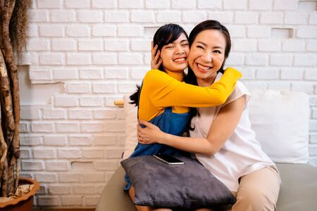 Loving smiling Asian women hugging happily while sitting together on couch at living room
