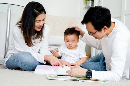 Happy modern Asian parents sitting on floor with cute infant boy and reading fairy tale while enjoying time together at home