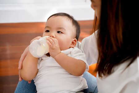 Close-up of Asian mother babysitting and feeding her own son with milk bottle in living room at home. - Motherhood and formula-fed newborn concept