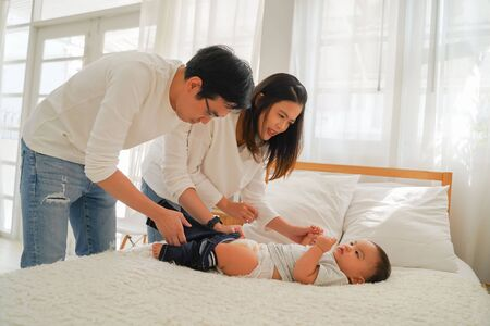 Young Asian father sitting on floor and holding infant boy while mother holding baby clothing and together taking care of son and changing diapers