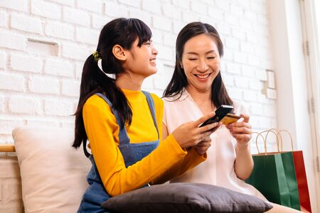 Happy smiling Asian woman and daughter in casual outfit browsing smartphone and using credit card while sitting on sofa with shopping bags