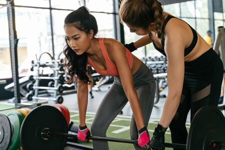 Asian personal trainer coaching a bodybuilding woman to perform the dead lifting exercise with barbell in the fitness gym. Weightlifting and workout training coach business concept