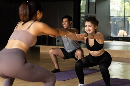 Group of happy Asian women and man doing squat exercises on yoga mats in aerobics class. Young sporty people smiling while working out in gym studio. Fitness Class Concept