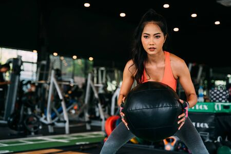 Determined and serious active Asian sportswoman squatting with medicine ball during work out in fitness club.