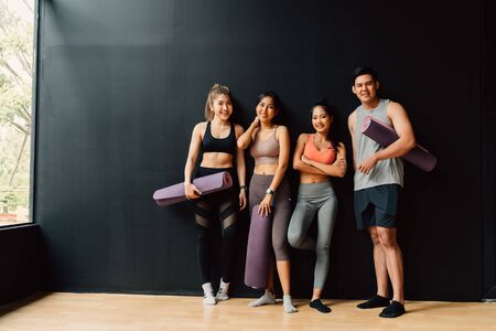 Happy smiling man and women looking at camera altogether in gym. Group of young people relaxing in gym after workout training with black background.
