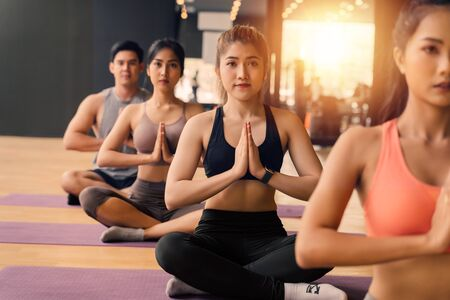 Group of Asian women and man doing pilates lying on yoga mats in aerobics class. Young sporty people on crossed legs on the floor and do namaste pose in gym studio