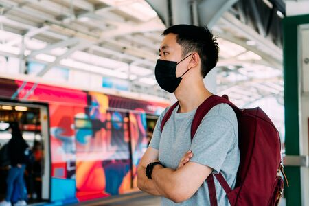 Close up of one young Asian man wearing a black surgical face mask waiting for the train during new type Coronavirus Covid-19 pneumonia outbreak and pm 2.5 smog air pollution crisis in big city.