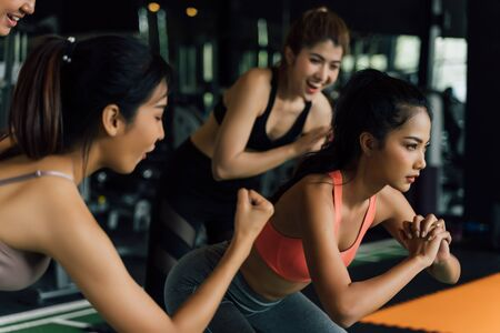 Group of people cheering on their Asian female friend doing squats in fitness gym. Working out together as a teamwork. Encouragement and togetherness concept