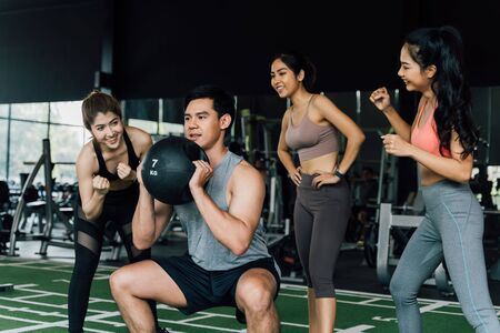 Group of people cheering on their Asian Chinese male friend doing squats with a medicine ball in fitness gym. Working out together as a teamwork. Encouragement and togetherness concept Imagens