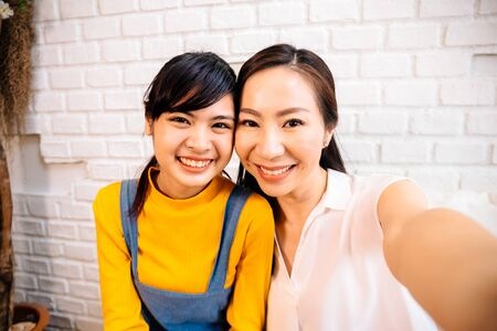 Face of smiling happy Asian teenage daughter and Asian middle-aged mother looking at mobile phone in indoor living room at home. It could be video calling or taking a selfie photo together.