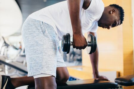 Side view of African American man in sportswear leaning on bench and doing row exercise with dumbbell during training in gym. 版權商用圖片
