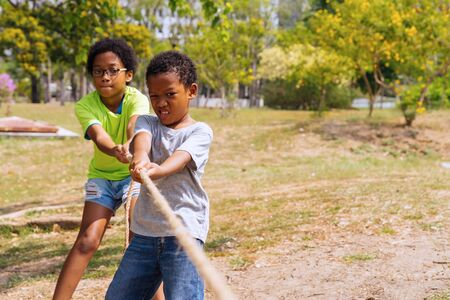 African American boy and girl pull rope together in tug of war competition - brother and sister on leisure activity - strength and teamwork concept