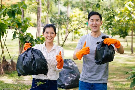 Cropped young happy Asian male and female couple volunteers with gloves giving thumbs up while collecting garbage waste into trash bag in green park. Environmental friendly and litter collection Banque d'images