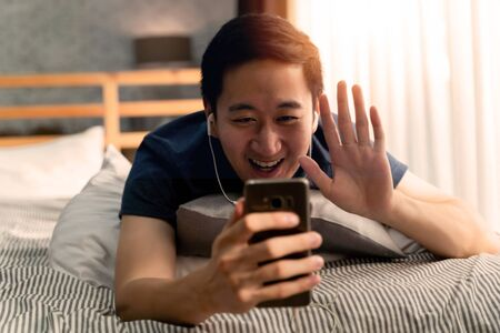Portrait of happy 30s aged Asian man making facetime video calling with smartphone at home. Hes waving on phone screen. Using conferencing meeting online app, social distancing, concept Stock fotó