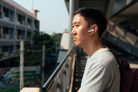 Close up of young man listening to music with wireless earpods while commuting by train at station. Asian guy enjoying music on the go.