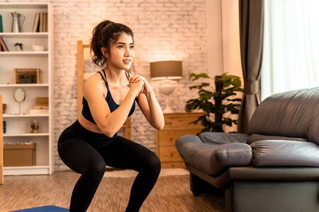 Young fit Asian woman working out at home. Beautiful female athlete training for legs muscles with squats exercise move. Фото со стока