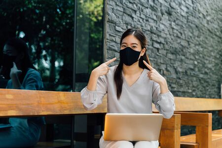 Asian woman wearing a face mask outside while sitting on laptop and pointin at her mask. Dont forget to wear a mask and face mask requirement to go outside concept.