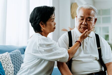 Unhappy retired Asian senior couple sitting on the sofa while elderly wife comforting her sad husband at home 版權商用圖片 - 148095146