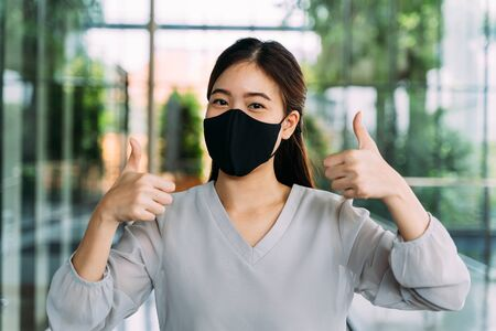 Young optimistic Asian female student giving thumbs up gesture. Shes wearing a protective mask (PPE) to avoid air pollution or Corona Virus pandemic for safety. Stockfoto