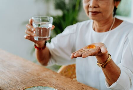 Senior Asian woman with a cup of water and pill taking remedy in cozy room at home. Old female taking medicine