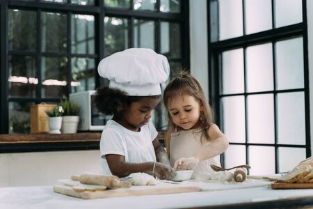 Diverse group of African American and Caucasian girls prepare the dough and bake cookies in the kitchen while learning in the class at school