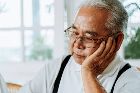 Stressed senior Asian male in glasses leaning on hand and pondering about problems at home. Elderly man thinking about something.