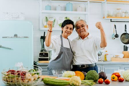 Senior Asian married couple cooking food at kitchen home. Elderly 70s man and woman looking at camera while preparing ingredients at kitchen counter together.