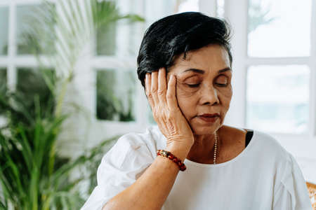 Stressed senior Asian female leaning on hand and pondering about problems at home. Elderly woman thinking about something.