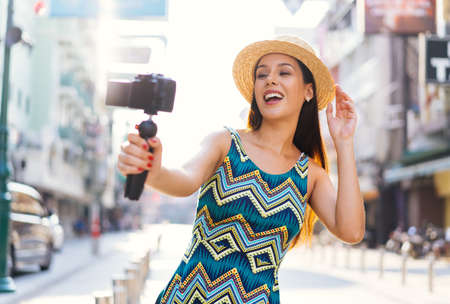 Young brunette woman using a video camera to record journey with smile. Happy and excited 20s Hispanic girl traveler wear summer dress with hat waving to internet audience. Influencer vlogging concept Stok Fotoğraf
