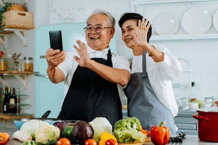 Cheerful elderly Asian man and woman smiling and greeting friend while making video call on smartphone and cooking in kitchen