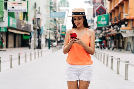 Young brunette woman using a mobile phone laughs in Bangkok, Thailand with attractive smile. Happy and excited Hispanic girl traveler wear summer clothes with hat in Asia. With Copy space