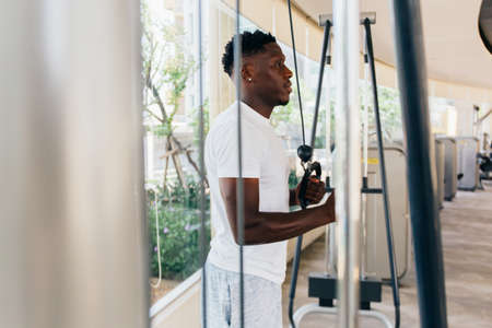 Muscular African American sportsman doing cable fly with exercise machine standing against window during training in gym.