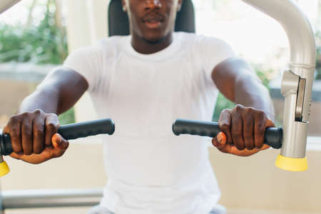 African American athlete doing exercise for chest muscles on pec deck machine during workout in gym.
