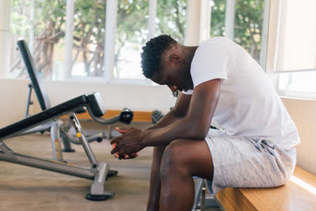Desperate African American male athlete sitting on bench during break in fitness training in modern gym Banque d'images - 151517146