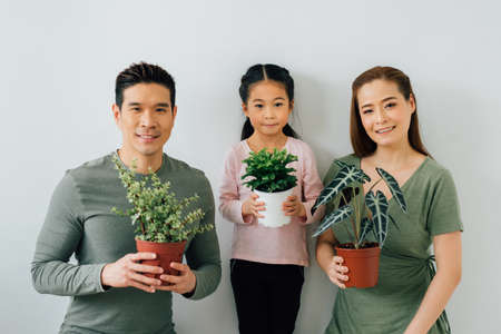 Chinese mother and father looking at camera with young daughter holding plants Stock fotó