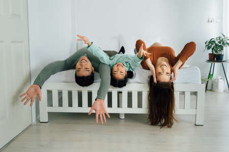Cheerful Asian mother and father with young daughter lying on backs on bed and looking at camera. Family togetherness and bonding indoors concept