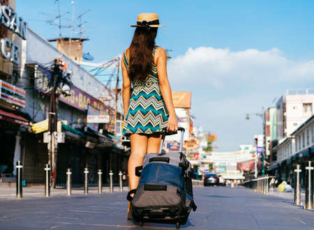 Rear view of young Hispanic Brunette woman on vacation with luggage on pedestrianised street