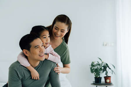 Asian mother and father looking away with young daughter indoors at home. Family bonding and happiness lifestyle concept.
