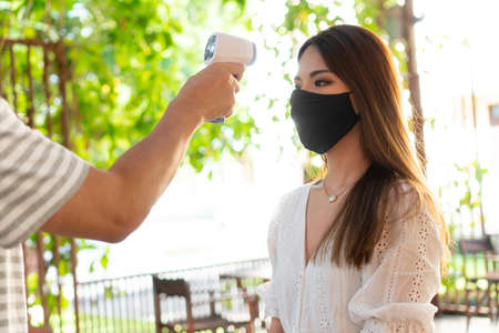 Close up hand using medical digital infrared thermometer on young woman in face mask to check and monitor body temperature. New normal life to screen visitors to prevent spread of Coronavirus COVID-19
